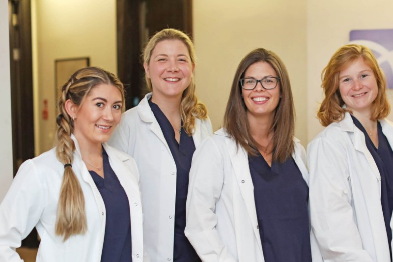 4 Female Embryologists in white coats standing and smiling