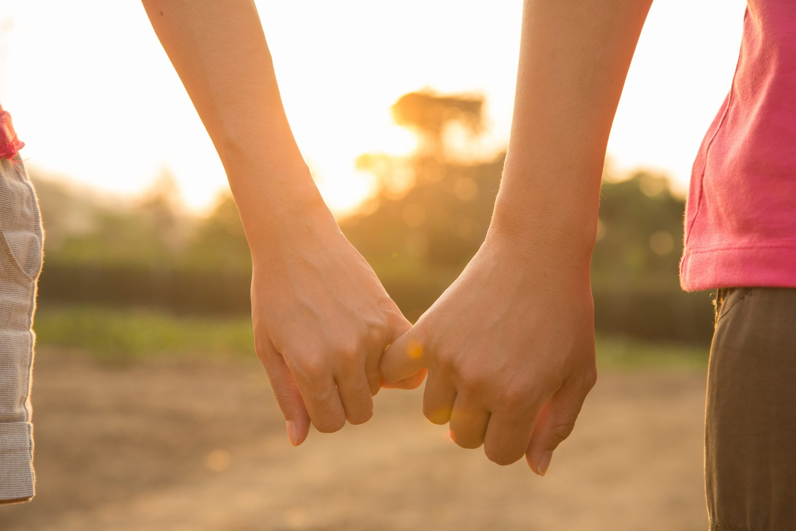 photo of couple holding hands with their little fingers